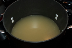 Maintain the chicken broth hot at a medium temperature